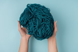 partial view of woman holding yarn f