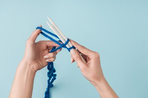 partial view of woman with blue yarn