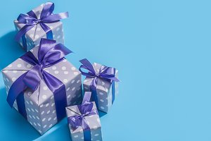 Gifts in holiday boxes on blue.