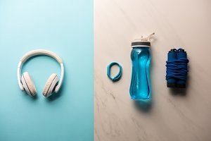 flat lay with headphones, bottle of