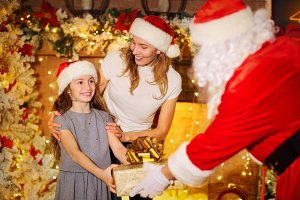 Santa Claus gives a gift to a girl