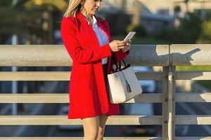 Blonde woman wearing red jacket usin
