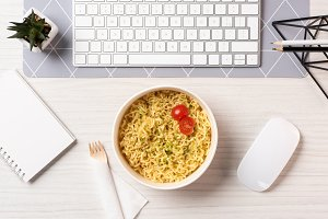 top view of bowl with noodles, fork,