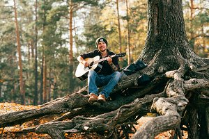 adult male playing acoustic guitar s