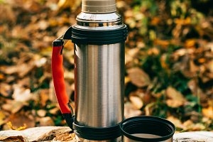 metallic camping thermos on beautifu