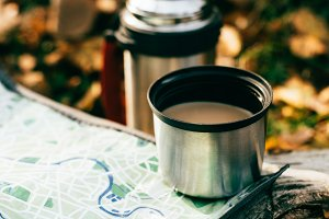 coffee in metallic thermos cup on tr