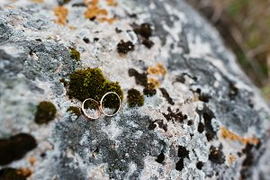 Wedding golden rings at stone with m