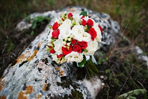 Wedding bouquet with rings at stone