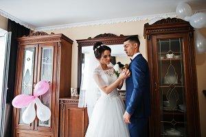 Gorgeous bride puts a buttonhole flo