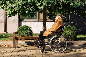 side view of senior disabled man sit