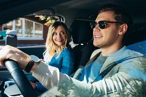 smiling woman at boyfriend driving c