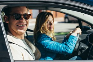 young woman driving car with boyfrie