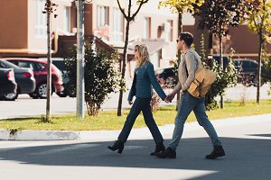 couple holding hands while walking t