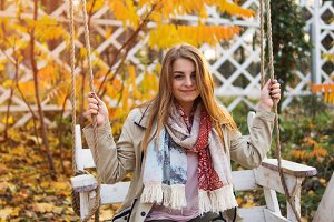 Cute young woman on a swing in autum
