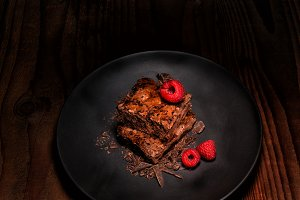 Two Brownies and Raspberries on a bl