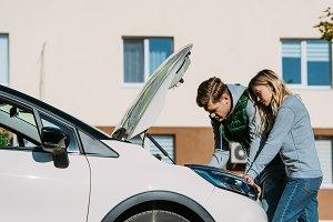 young couple repairing broken car on