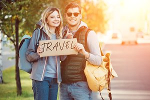 happy young couple of travelers hold