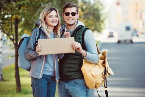 happy young couple with backpacks ho