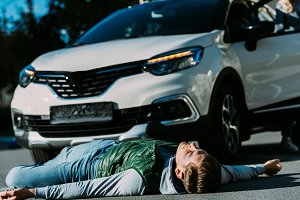 injured young man lying near car on