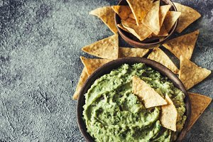 Guacamole in bowl with tortilla chip