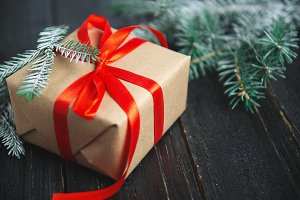 Gift box with a red ribbon on a wood