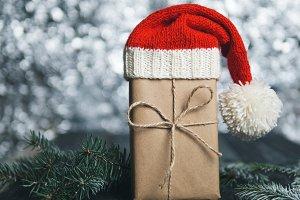 Christmas gift in Santa hat on bokeh