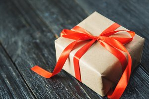 Square gift box with red ribbon on d