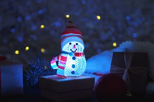 Snowman with gifts at night on new y