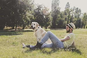 Young man resting with his dog on th