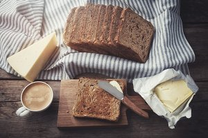 Toasts, butter, cheese, coffee cup.