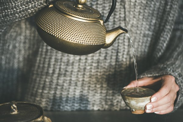 Female in sweater pouring green tea