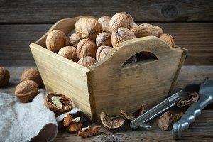 Walnuts in wooden crate, nutcracker.