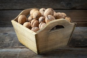 Walnuts in a wooden crate on table.
