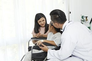 Asian male doctor talking to young c