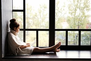 Pensive girl sitting on sill