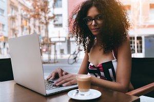 Woman in glasses, laptop, street bar