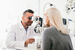 Optician examining woman's eyes with