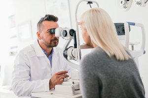 Optician checking his patient's eyes