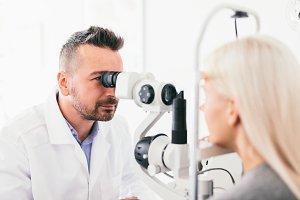 Optician examining his patients eyes