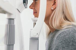 Woman taking eyesight test at optici
