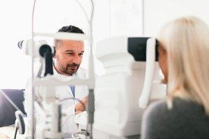 Optician examining his patient's eye