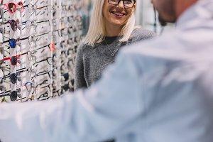 Woman and optician choosing glasses