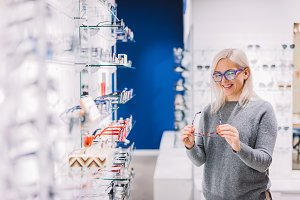 Woman looking at glasses at optic st