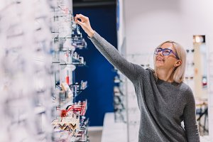 Woman choosing glasses at optic stor