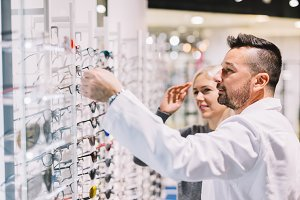 Optician and his patient choosing gl