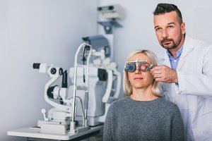 Optician examining woman's eyes.
