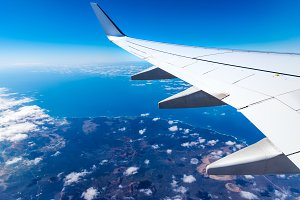 Wing of airplane above island with