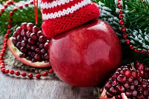 Red apple in hat and pomegranate