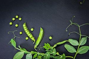 Green peas on black slate background