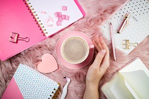 Female hand, coffee cup, notebooks